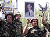 In a photo taken during a guided government tour, Syrian soldiers raise their weapons while holding a picture of President Bashar Assad as they leave the eastern city of Deir al-Zour on Aug. 16, following a 10-day military operation.
